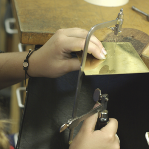 Young womans hands sawing sheet metal with jewllers sawframe on a jewellers peg
