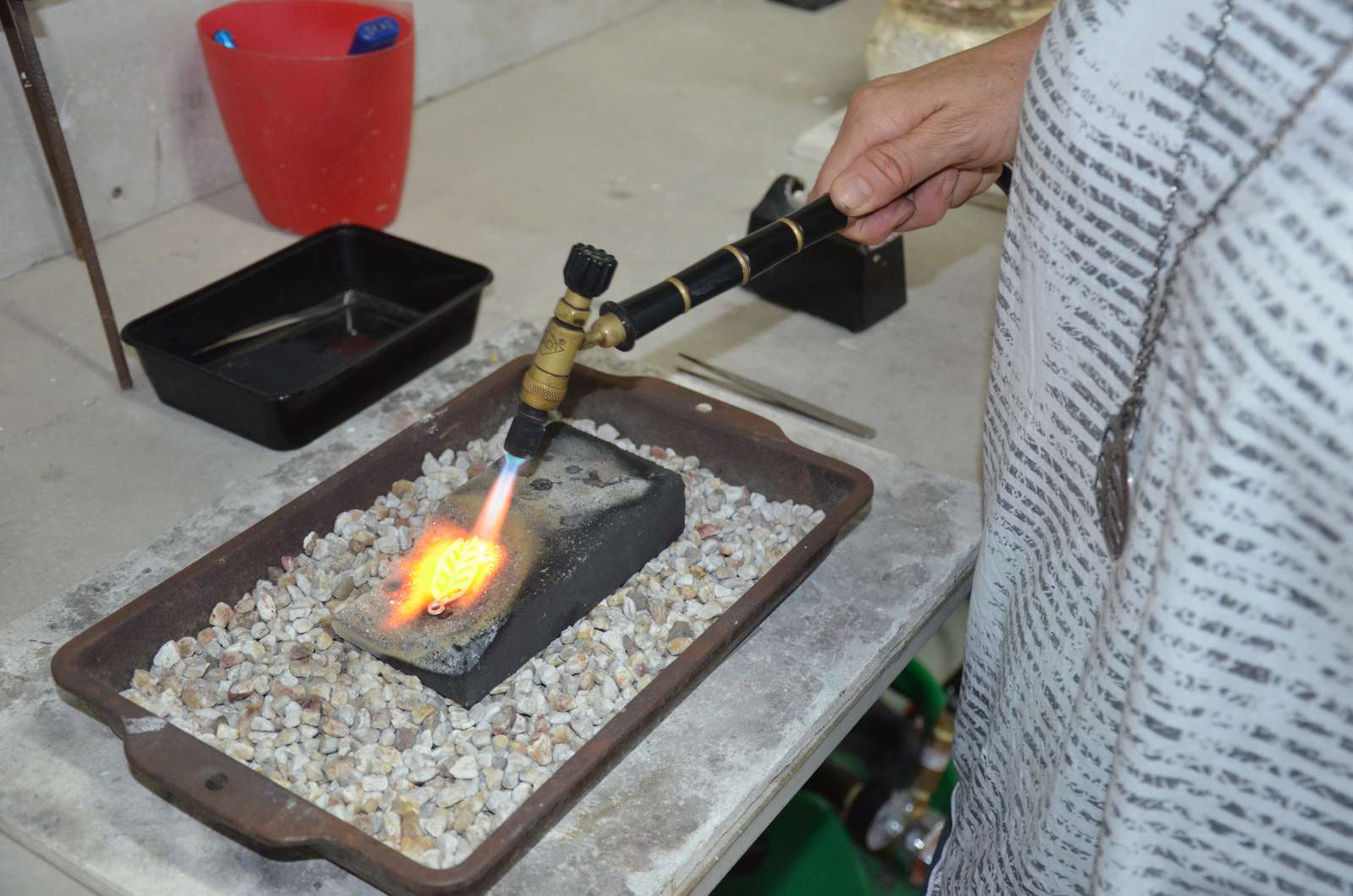 Student learning how to melt silver into balls on a charcoal block