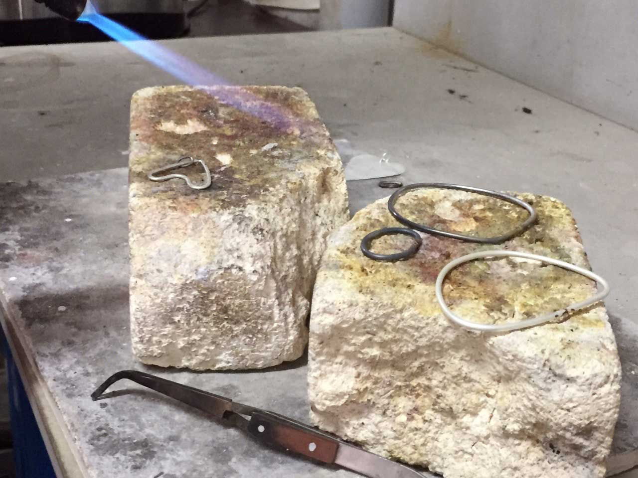 Using a torch to solder silver jewellery in Advanced Jewellery Course