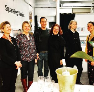 Resident Artists of SquarePeg smiling in group shot at a pop up shop event in the studios gallery space