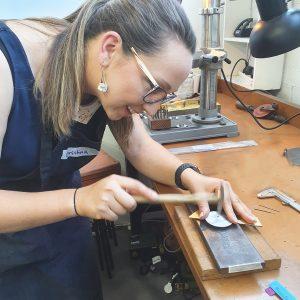 Student hammering a rivet into sheet metal at SquarePeg Studios