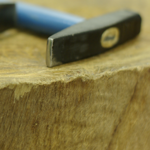 Close up of hammer head on a wooden stump