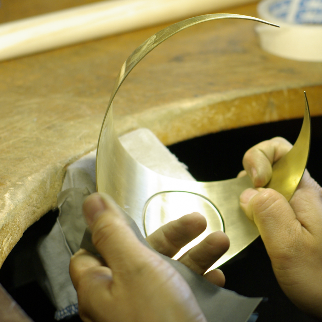 Hands making a metal object on jewellers peg
