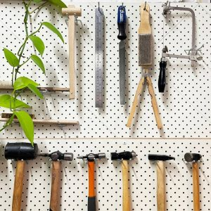 White pegboard with jewellery tools and a trailing green ivy