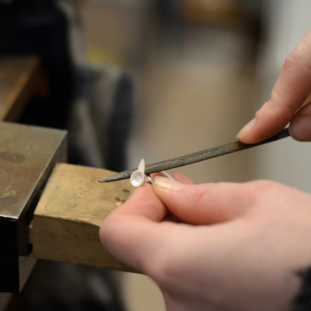 Hand filing a ring on a jewellers peg at SquarePeg Studios